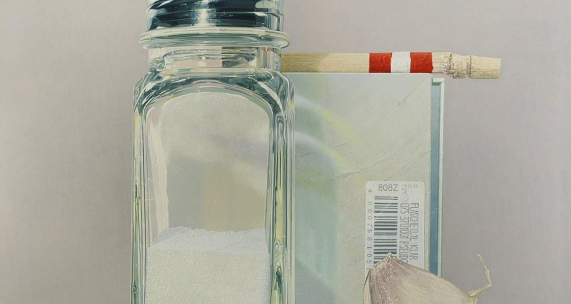 Das Stillleben des Künstlers Rolf Gith zeigt eine vierteilige Objektgruppe bestehend aus Knoblauchzehe, Salzstreuer, Pappschachtel und Holzstab. Der Bildraum ist hell und von Licht durchflutet.