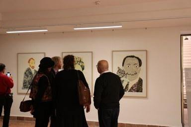 Eine kleine Personengruppe im Gespräch vor den Kunstwerken von Perihan Arpacilar. Die Künstlerin steht in der Mitte, jedoch mit dem Rücken zum Betrachter.