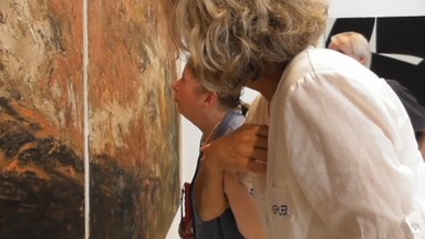 Beim genauen Betrachten eines Kunstwerks von Adnan Abd Al-Rahman. Ein Frau mit starken Seheinschränkungen tritt in Begleitung nah an das Bild heran, um es zu erfassen.