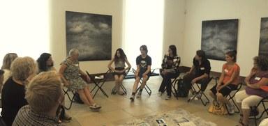 Eine Gruppe sitzt im Stuhlkreis im Foyer des Museums. Die Künstlerin Doris Conrads leitet hier einen Kreativworkshop zum Thema