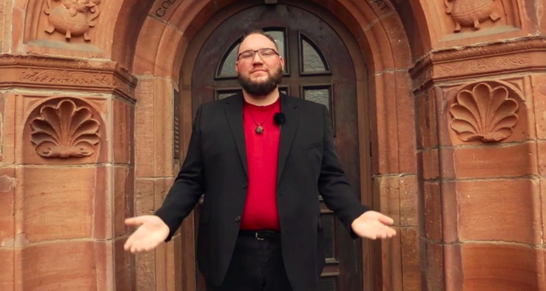 Ein Mann steht vor dem Portal der Hessischen Stipendiatenanstalt. Er hält seine Arme zu einer Segensgeste ausgebreitet.