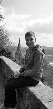 Der Mitbewohner Max sitzt auf der Schlossmauer im Paradiesgarten.