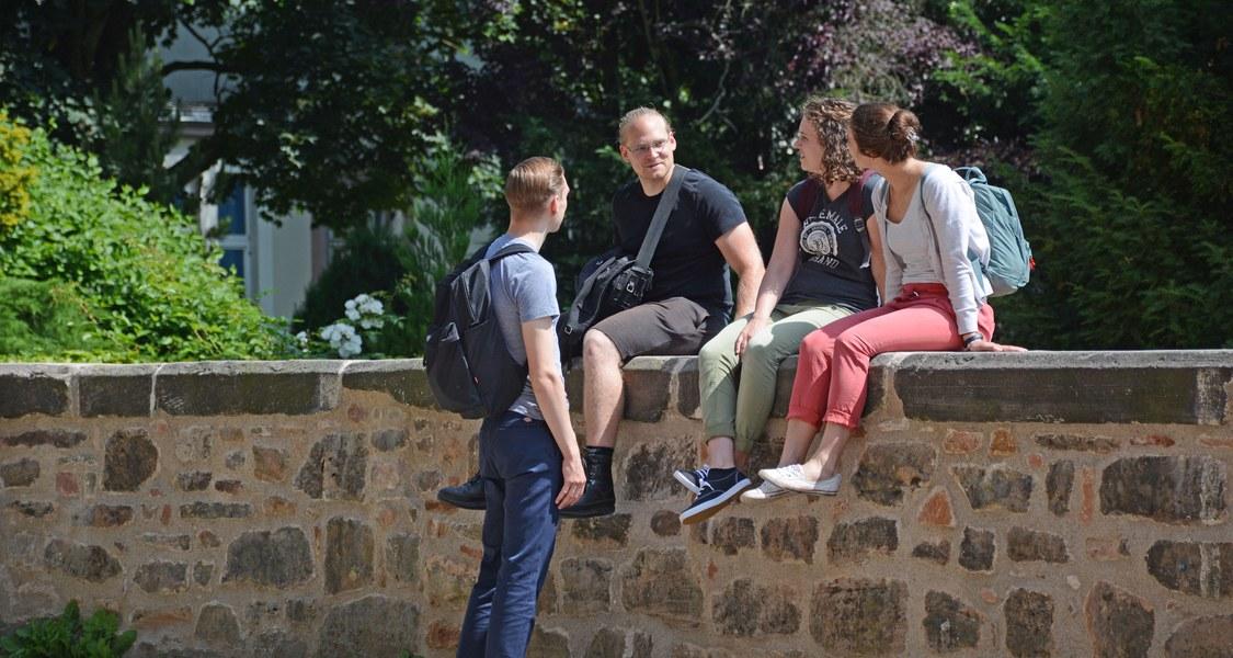 Studierende unterhalten sich vor dem Gebäude der Religionskundlichen Sammlung