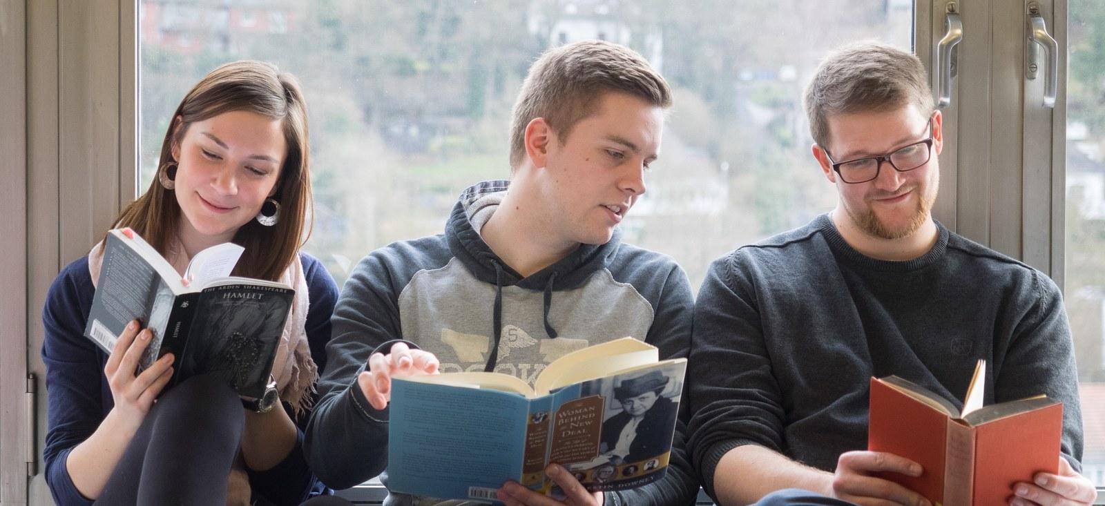 Studierende lesend auf Fensterbank