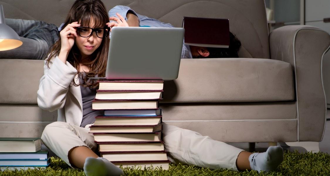 Foto einer Studentin vor einem Bücherberg