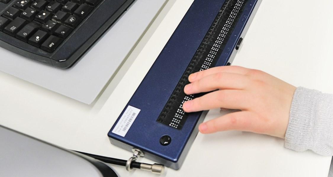 Foto: Hand, die eine Braillezeile bedient