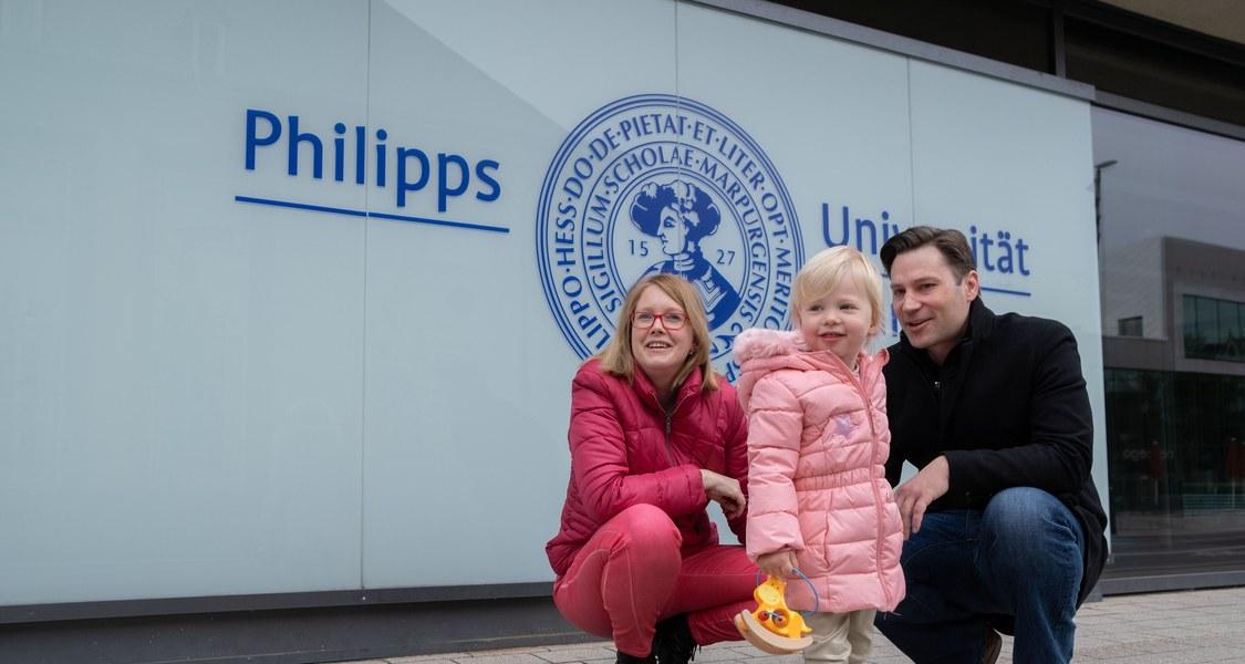 Eltern knien mit kleiner Tochter unter dem Logo der Philipps-Universität.