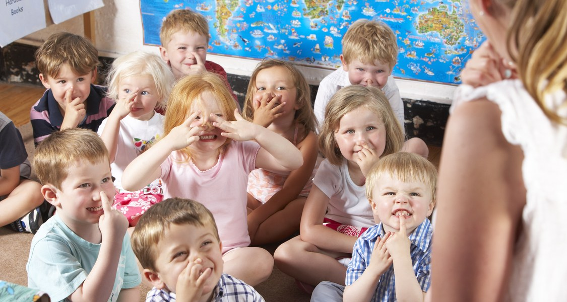 Kindergruppe im Kindergarten SCHNEIDET Grimassen: