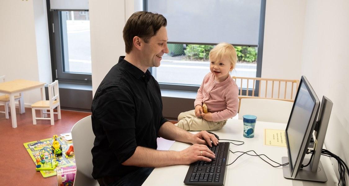 Vater arbeitet am PC, während Tochter neben ihm auf dem Tisch sitzt und lacht.