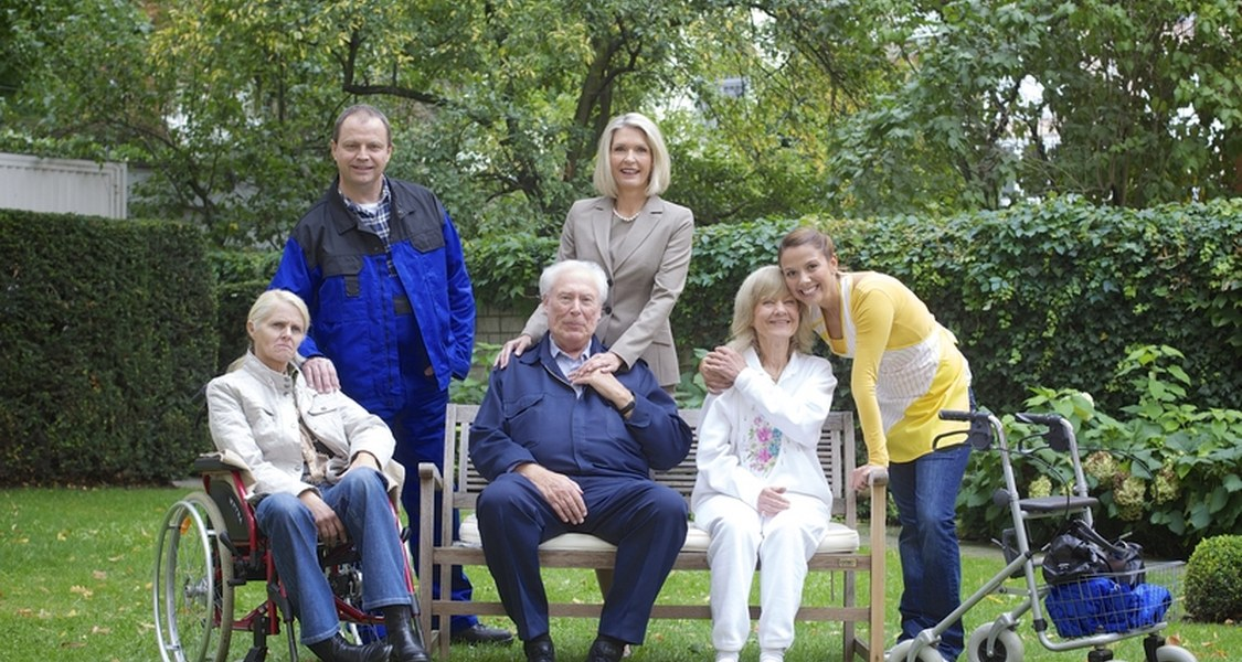 Jüngere und ältere Menschen, stehend oder sitzend, teilweise im Rollstuhl, mit Rollator oder Gehhilfen.