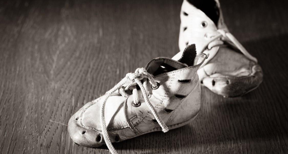 Schwarzweiß-Aufnahme von alten Kinderschuhen.