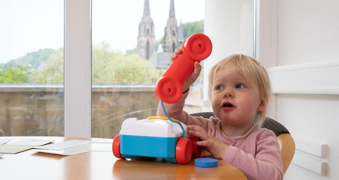 Kind spielt mit Kinder-Telefon und hinter dem Fenster die Elisabethkirche.