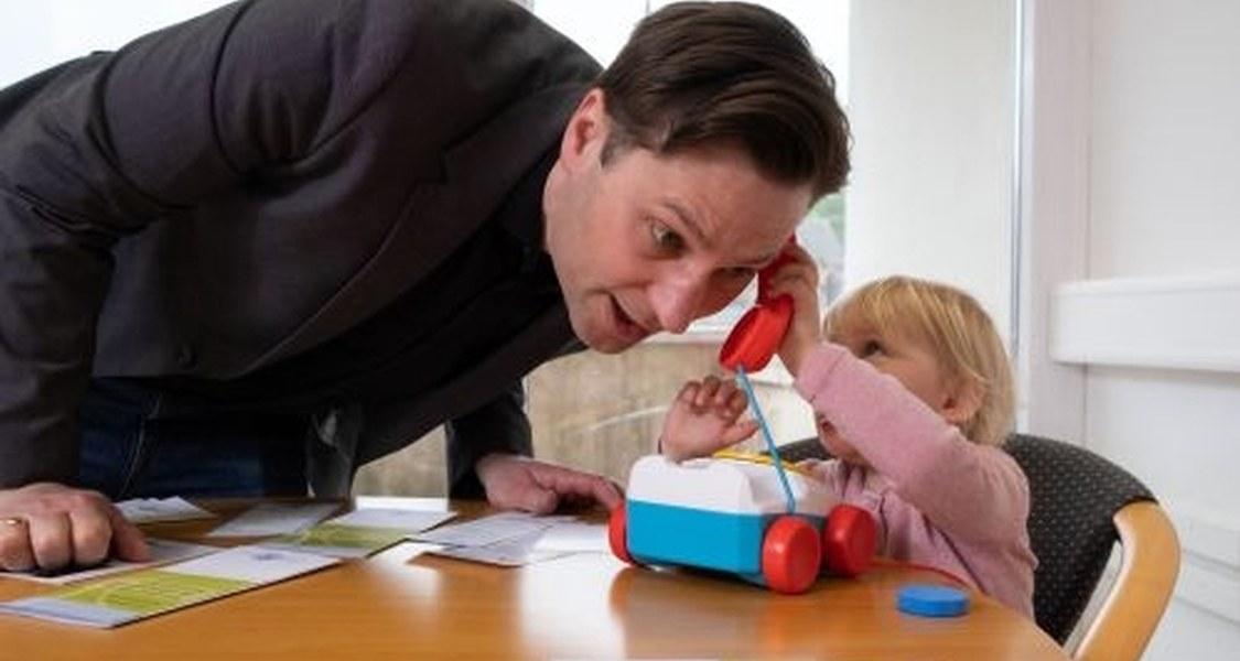 Kind und Vater spielen mit Kindertelefon.