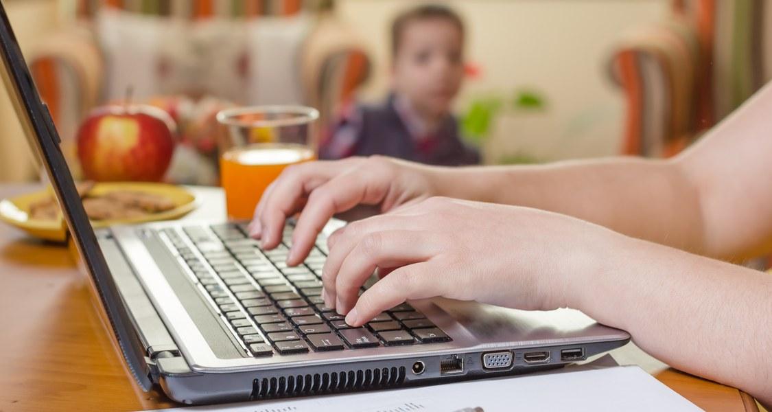Das Bild zeigt eine Tastatur eines Laptops, auf der gerade eine Person etwas eintippt. Der Laptop steht auf einem Tisch und im Hintergrund ist ein Glas mit Fruchtsaft, ein Apfel und ein Kind zu erkennen.