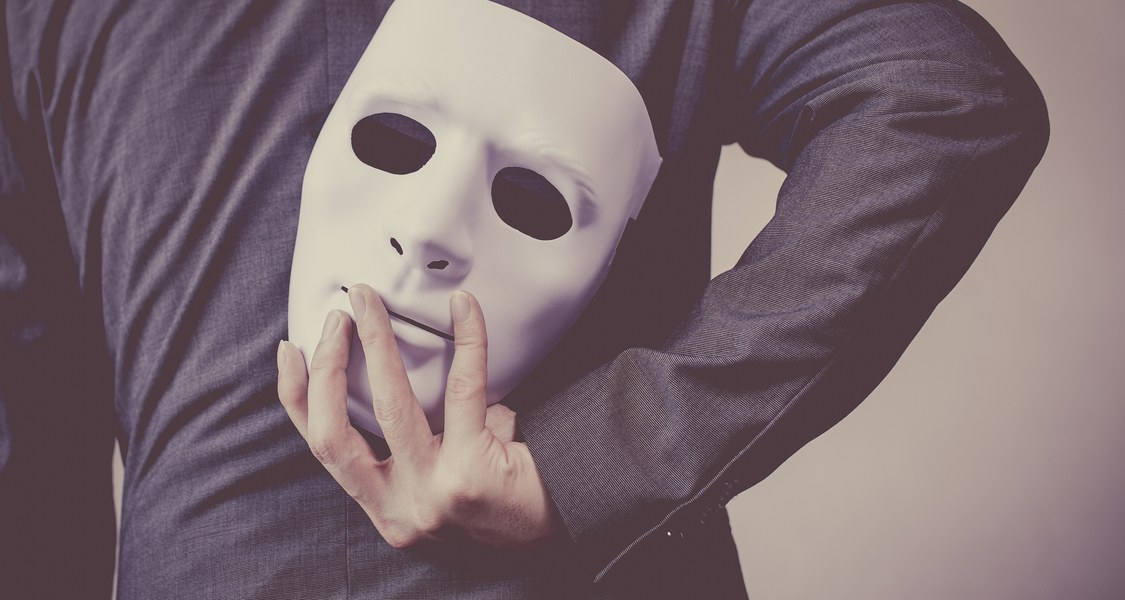 Auf dem Bild ist eine weiße Gesichtsmaske zu sehen, die jemand hinter den Rücken hält.