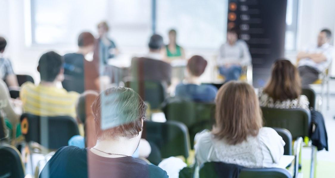 Das Publikum lauscht dem Handeln in einer Konferenzhalle