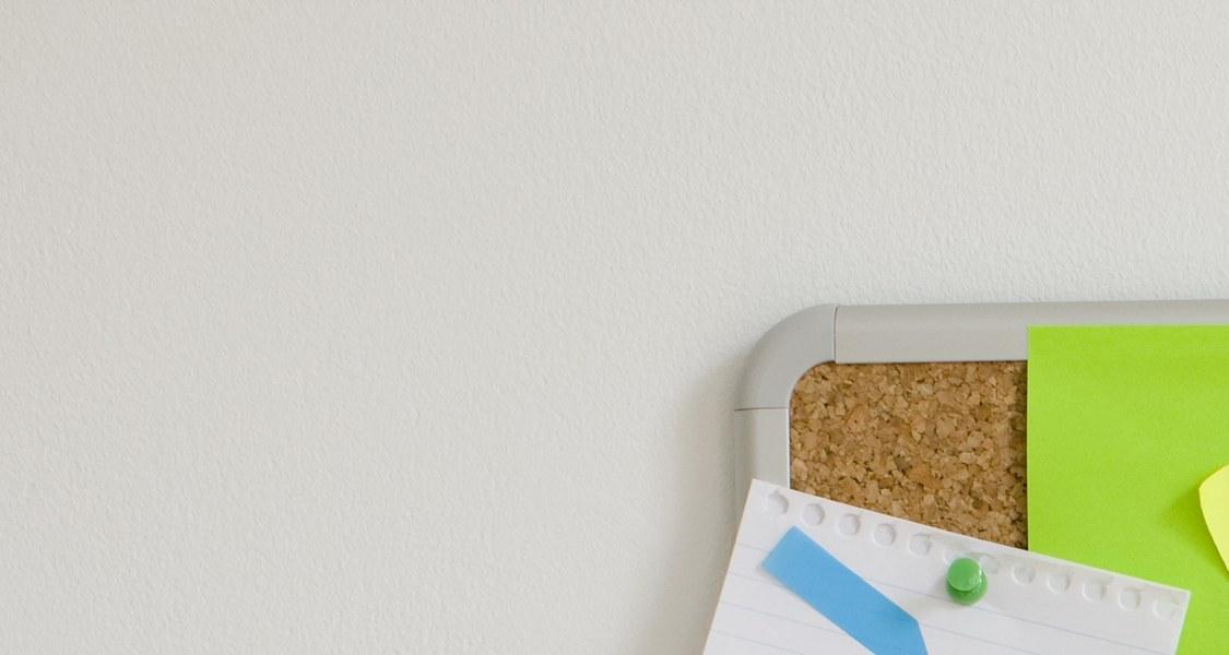 """Auf dem Bild ist eine braune Korkpinnwand mit zahlreichen sich teilweise überlappenden Post-It Klebezetteln in verschiedenen Farben zu sehen. Das mittlere Post-it trägt die Aufschrift """"Make things happen"""", englisch für """"Mache Dinge geschehen"""" oder """"Sorge dafür, dass Dinge passieren""""."""