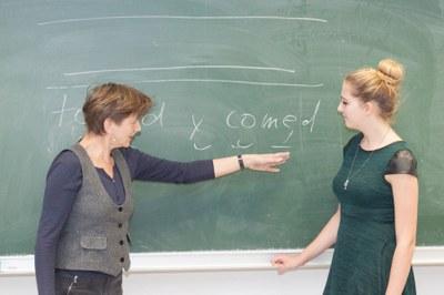 Lehrende und Studentin erörtern an der Tafel