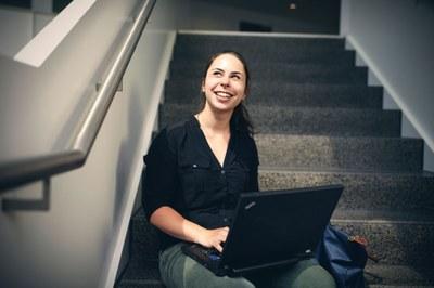 Studentin auf Treppe mit Laptop