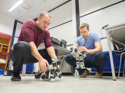 Studierende arbeiten mit kleinen Robotern