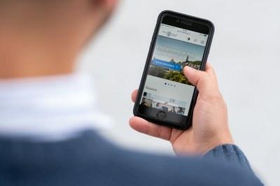 Eine Hand hält ein Smartphone, auf dem die Website der Philipps-Universität geöffnet ist.