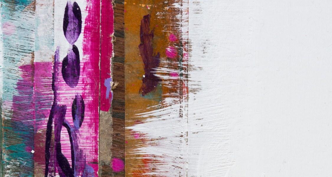 Zu sehen sind blaue, orangene und rosa Farbreste auf Holz.
