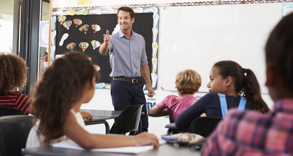 Ein Lehrer steht vor einer Klasse. Der Beobachtende befindet sich unter den Schüler/innen. Durch seine Handbewegung scheint der Lehrer jemanden aufzurufen, er lächelt dabei freundlich. Die Lernenden, welche zu sehen sind, scheinen in etwa 10 Jahre alt zu sein.