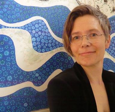 Professorin Anika Oettler vor einem weiß-blauen abstrakten Bild