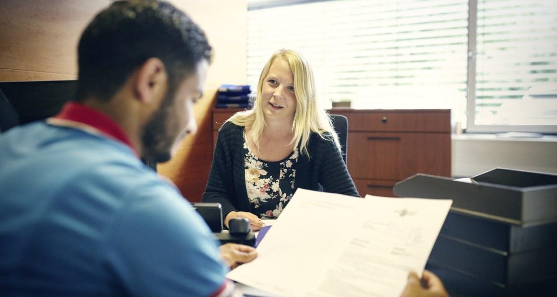 Student im Studierendensekretariat beim Betrachten von Dokumenten, mit einer Beraterin auf der gegenüberliegenden Tischseite