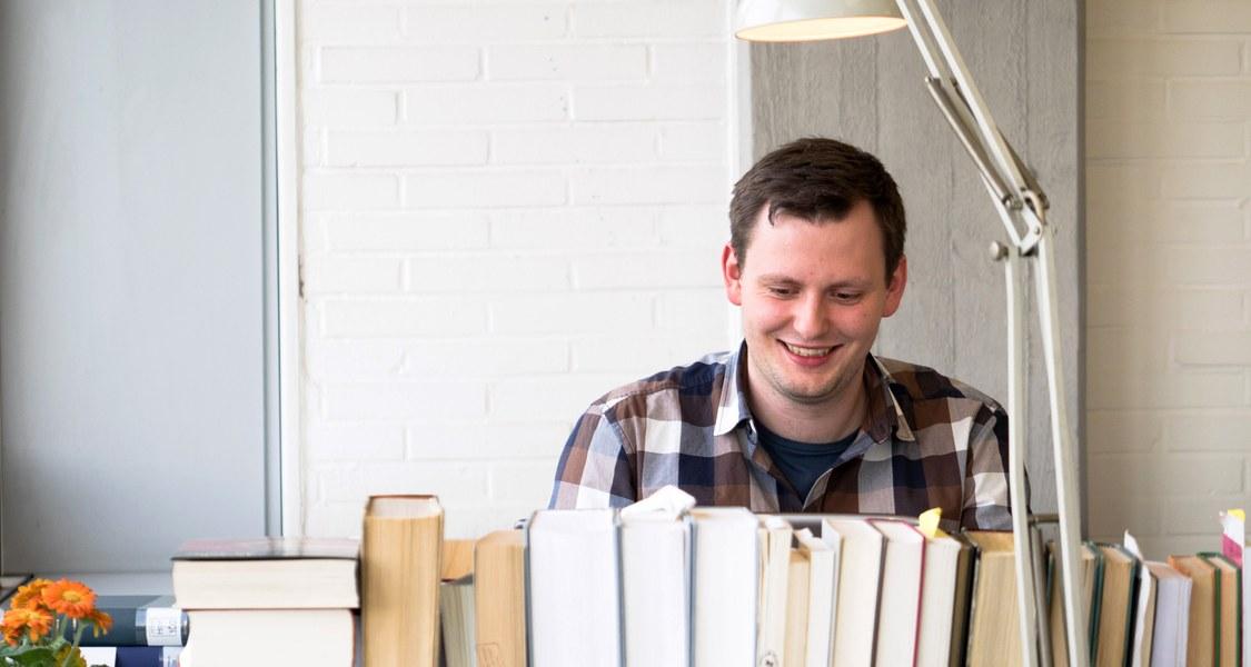 Studierender unter einer Lampe an einem Arbeitsplatz mit einer langen Reihe Bücher ringsherum.