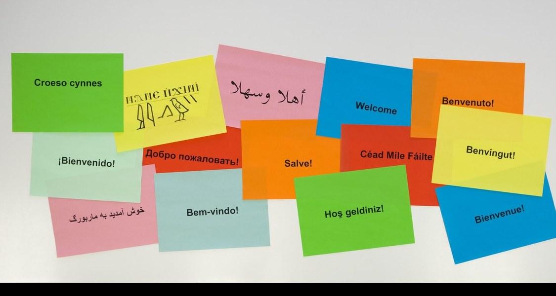 """Mehrere bunte Zettel auf Whiteboard mit Aufdruck """"Willkommen"""" in verschiedenen Sprachen."""