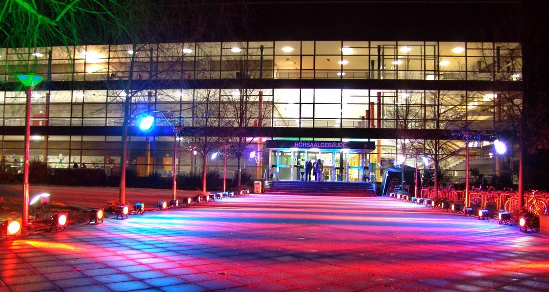 Blick auf den Haupteingang des Hörsaalgebäudes bei Nacht.