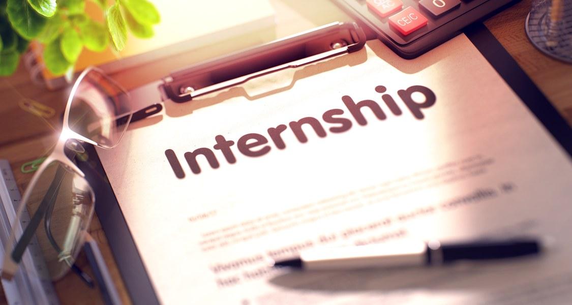 """Ein Vertrag mit dem Wort """"Internship"""" als Überschrift, umgeben von einem Stift, einem Taschenrechner und einer Brille."""