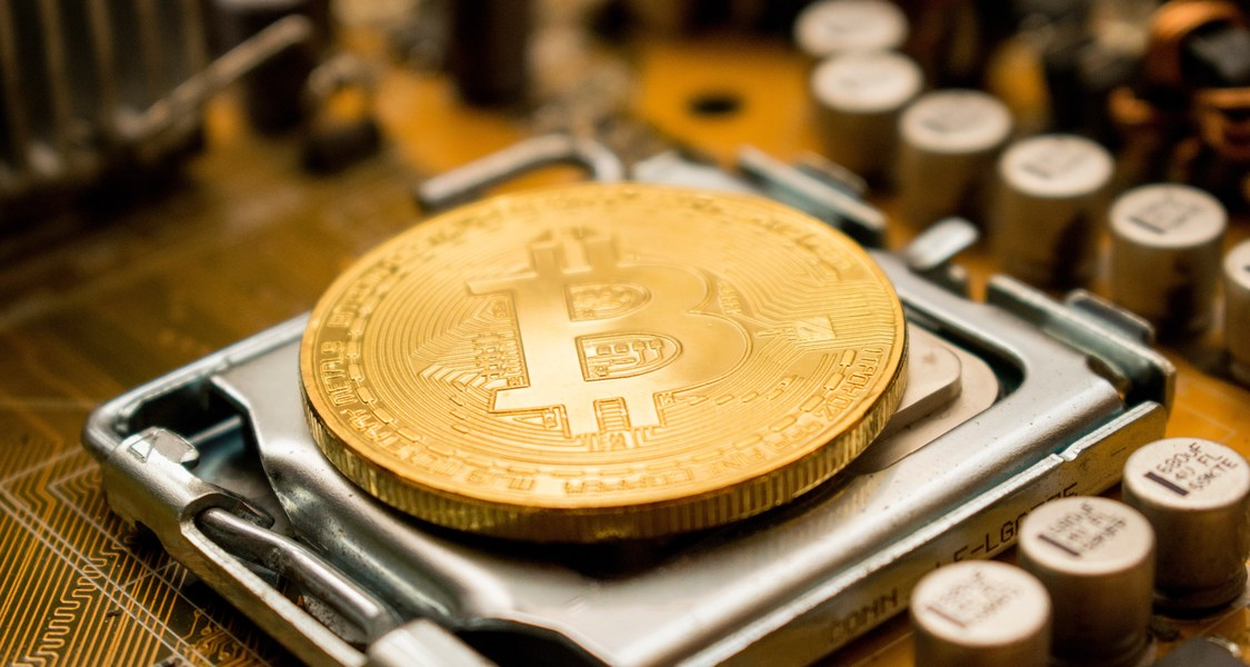 A large gold coin with the BitCoin-logo placed on a CPU.