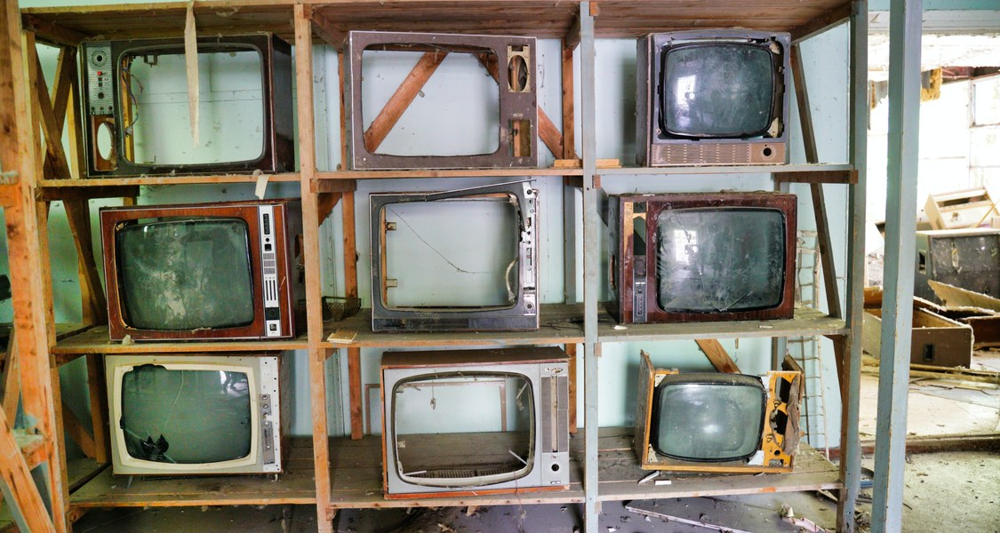 A dilapidated room with an shelf containing 9 broken televisions.