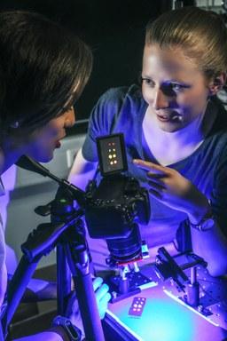 Zwei Forschende der AG Halbleiterphotonik begutachten Polymerproben, die mit dem Fluoreszenzfarbstoff Nile Red angefärbt und mit blauem Licht beleuchtet wurden. Man kann erkennen, dass unterschiedliche Polymertypen in unterschiedlichen Farben leuchten.