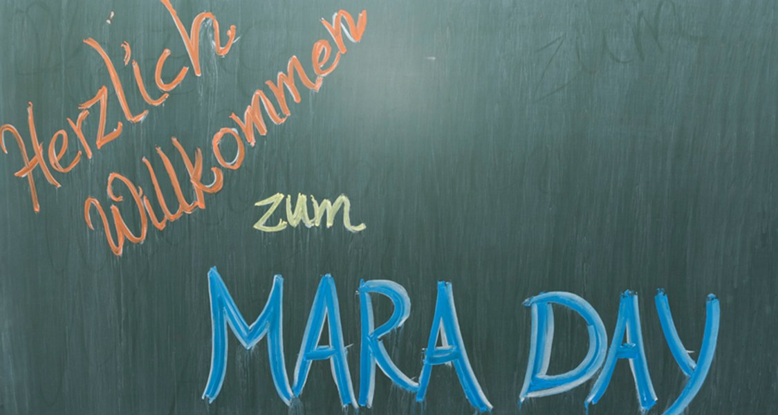 """Welcome to MARA DAY"" written on a chalkboard"