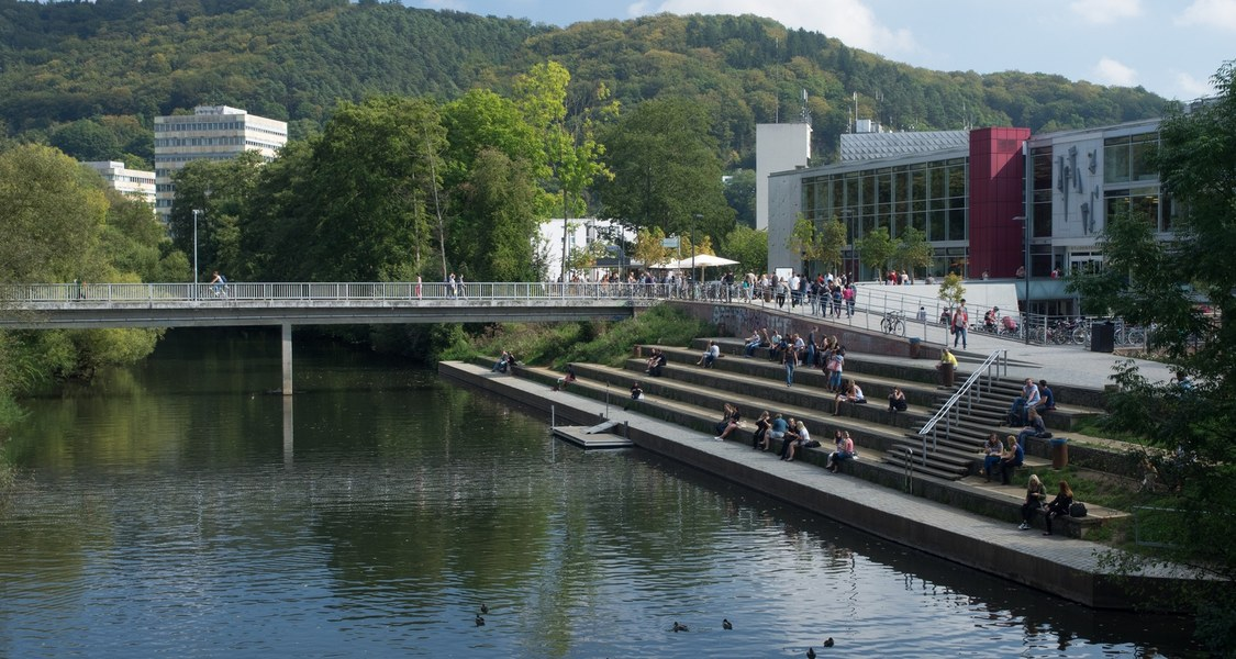 The student union and humanities building in the summer sunshine, flanked by the Lahn and the Lahnberge.