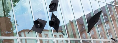 Doctor´s hats thrown in the air in front of the glass facade of the university library in Marburg.